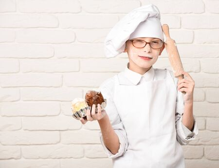 nudelholz: young boy cute cook chef in white uniform and hat on stained face flour with glasses holding chocolate cakes and rolling pin on brick wall background, copy space