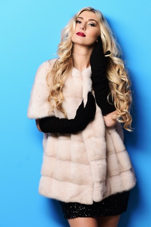 velvet dress: young fashionable sexy pretty woman with beautiful long curly blonde hair in waist coat of white fur and black velvet gloves on blue studio background Stock Photo