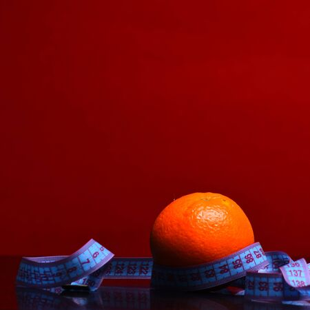 orange with measurement tape around in red background, copy space Stock Photo