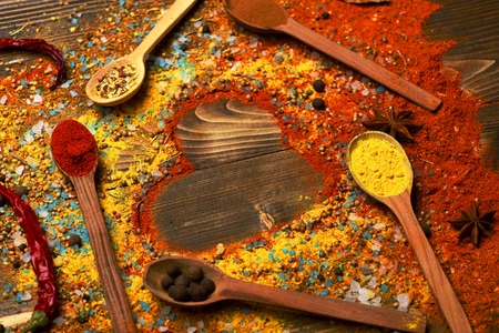 spiciness: valentine set of ingredients for cooking fragrant spices in spoons with allspice, coriander and pepper and chili pepper and paprika in form of heart on vintage wooden background, copy space