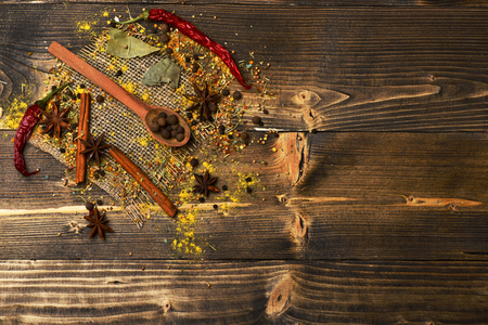 set of ingredients for cooking spicy fragrant spices in spoons with allspice, cinnamon and pepper, star anise lies on sackcloth on vintage wooden background, copy space