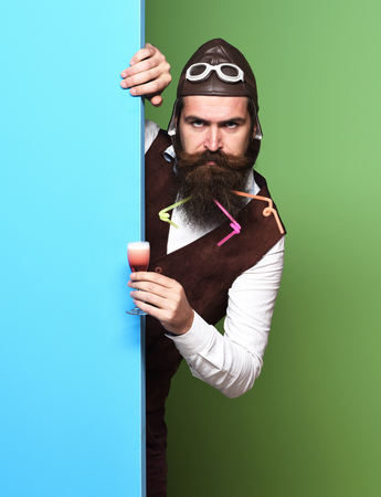 handsome bearded pilot or aviator man with long beard and mustache on serious face holding glass of alcoholic shot in vintage suede leather waistcoat with hat and glasses on colorful studio background