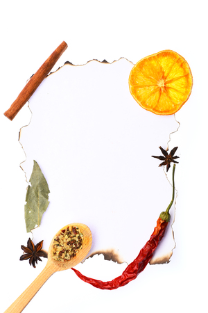 spiciness: set of ingredients for cooking spicy fragrant spices with dried orange and spoon and cinnamon and chili pepper lie on white paper for notes on white paper background, copy space Stock Photo