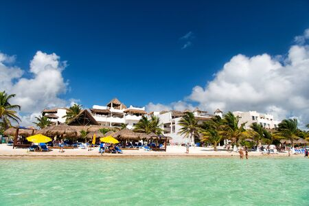 sunbeds: Mexico, Costa Maya - February 1, 2016: tropical beach at transparent sea or ocean water with sunbeds on white sand with green palms tourist resort on sunny summer day on blue sky
