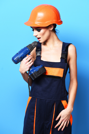 pretty cute sexy builder girl or brunette woman with fashion makeup on serious face in orange uniform with hard hat or helmet holding tool or putty knife and brick on blue studio background