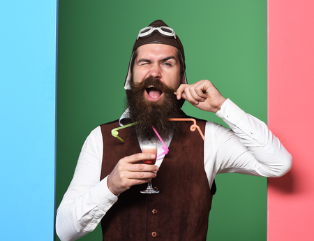 handsome bearded pilot or aviator man with long beard and mustache on funny face holding glass of alcoholic shot in vintage suede leather waistcoat with hat and glasses on colorful studio background