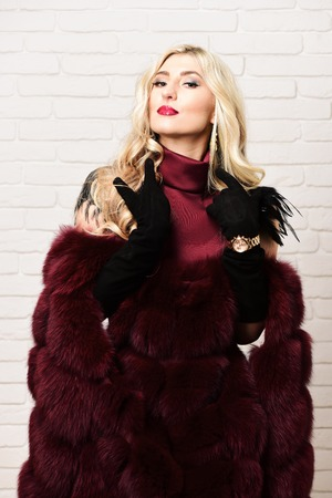 velvet dress: young fashionable sexy pretty woman with beautiful long curly blonde hair in waist coat of burgundy fur and red dress on slim body and black velvet gloves on brick wall studio background