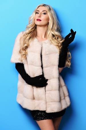 young fashionable sexy pretty woman with beautiful long curly blonde hair in waist coat of white fur and black velvet gloves on blue studio background Stock Photo