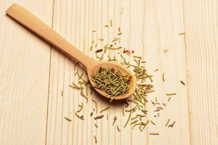 lactic: aromatic rosemary in spoon used in cuisine on lactic vintage wooden background, side view