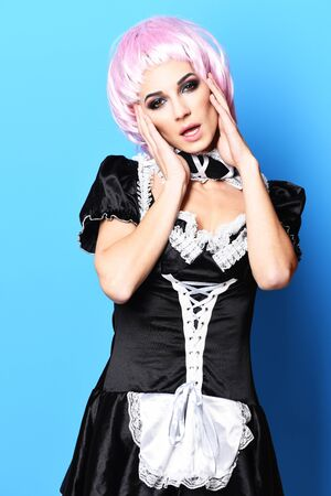 sexy maid: pretty cute sexy girl or beautiful young woman with fashion makeup in pink wig and black waitress or maid uniform on slim body touching face on blue studio background Stock Photo