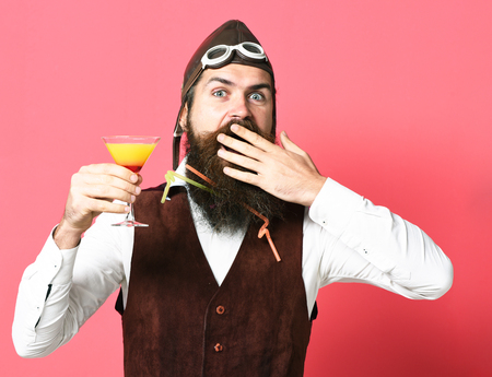 handsome bearded aviator man with long beard and mustache on surprised face holding glass of alcoholic beverage in vintage suede leather waistcoat with hat and glasses on red studio background Stock Photo