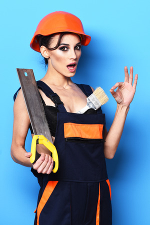 girl tied: pretty cute sexy builder girl or brunette woman with fashion makeup on surprised face in orange uniform with tied up hair in bun and hard hat or helmet holding saw on blue studio background Stock Photo