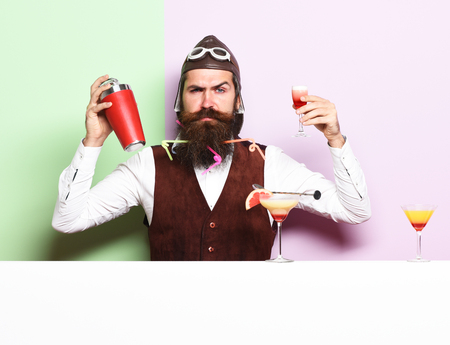 handsome bearded aviator or pilot with long beard and mustache on serious face with shaker alcoholic cocktail in vintage suede leather waistcoat with hand and glasses on purple green studio background Reklamní fotografie