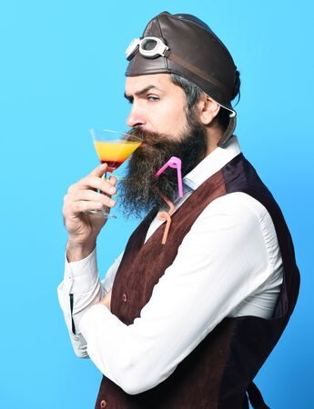 handsome bearded pilot or aviator man with long beard and mustache on serious face holding glass of alcoholic beverage in vintage suede leather waistcoat with hat and glasses on red studio background