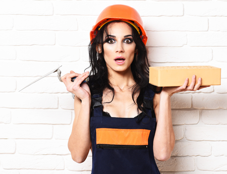 pretty cute sexy builder girl or brunette woman with fashion makeup on surprised face in orange uniform and helmet with curly long black hair holding brick and putty knife on white wall background