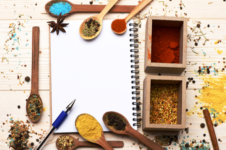 lactic: aromatic colorful spices in boxes and spoons with star anise cinnamon used in cuisine white copy book and pen on lactic vintage wooden background, copy space Stock Photo