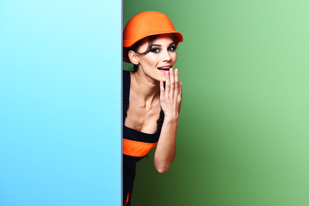 girl tied: pretty cute sexy builder girl or brunette woman with fashion makeup on surprised face in orange uniform with tied up hair in bun and hard hat or helmet on blue green studio background, copy space