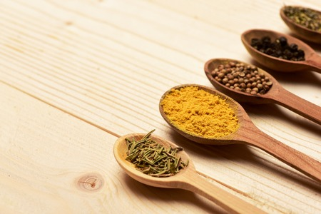 lactic: set of various aromatic colorful spices in spoons laid out in line used in cuisine on lactic vintage wooden background, copy space