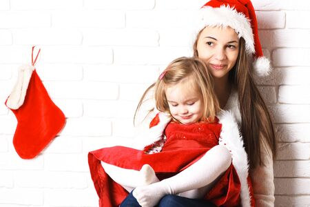 knee boots: young cute little blonde girl in christmas red dress and coat sitting on her mothers lap in xmas hat and long brunette hair with decorative stocking or boot on white brick wall background Stock Photo
