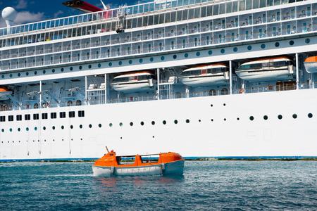 orange nassau: Nassau, bahamas - February 18, 2016: white cruise ship or liner with orange safety life or rescue boat on blue sea or ocean water surface on sunny day on beautiful seascape
