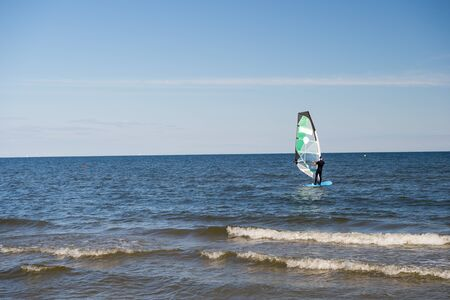 inshore: Gdansk, Poland - September 19, 2016: windsurfer or man sportsman surfs and sails on board by wind on sea water waves surface inshore on sunny day on blue sky Editorial