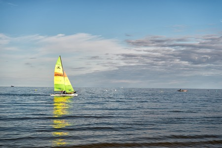 inshore: Gdansk, Poland - September 19, 2016: modern yacht or sailing boat or vessel sails by wind on sea water waves surface inshore on blue sky