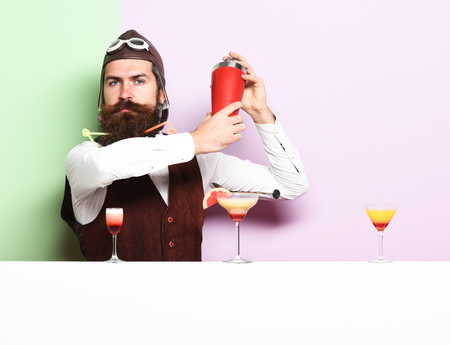 handsome bearded aviator or pilot with long beard and mustache on serious face with shaker alcoholic cocktail in vintage suede leather waistcoat with hand and glasses on purple green studio background Stock Photo