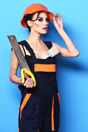 pretty cute sexy builder girl or brunette woman with fashion makeupon serious face in orange uniform with tied up hair in bun and hard hat or helmet holding saw on blue studio background