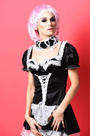 sexy maid: pretty cute sexy girl or beautiful young woman with fashion makeup on satisfied face in pink wig and black waitress or maid uniform on slim body on red studio background Stock Photo