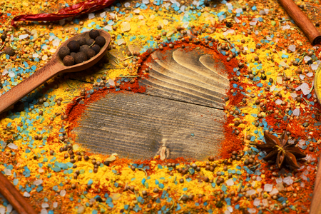 spiciness: valentine set of ingredients for cooking spicy fragrant spices in spoons with allspice, cinnamon and pepper and star anise in form of heart on vintage wooden background , copy space