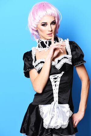 sexy maid: pretty cute sexy girl or beautiful young woman with fashion makeup on serious face in pink wig and black waitress or maid uniform on slim body touching mouth by finger on blue studio background Stock Photo