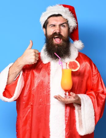 handsome bearded santa claus man with long beard on funny face holding glass of nonalcoholic cocktail in christmas or xmas sweater and new year hat showing cool on blue studio background Stock Photo