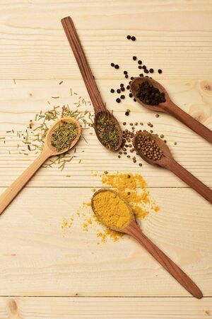 lactic: set of various aromatic colorful spices in spoons used in cuisine on lactic vintage wooden background, top view