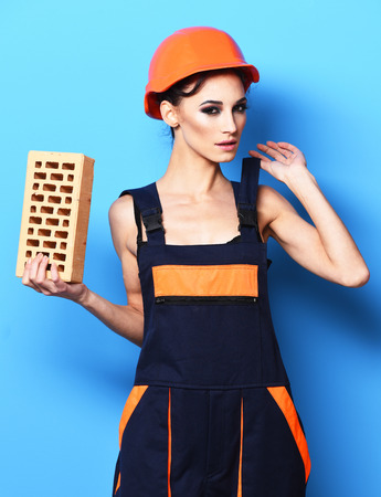 tied in: pretty cute sexy builder girl or brunette woman with fashion makeup on serious face in orange uniform with tied up hair in bun and hard hat or helmet holding brick on blue studio background Stock Photo
