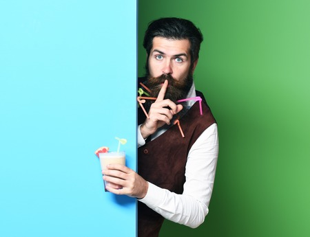 handsome bearded man with long beard and mustache has stylish hair on surprised face holding glass of alcoholic beverage in vintage suede leather waistcoat on blue green studio background, copy space Stock Photo