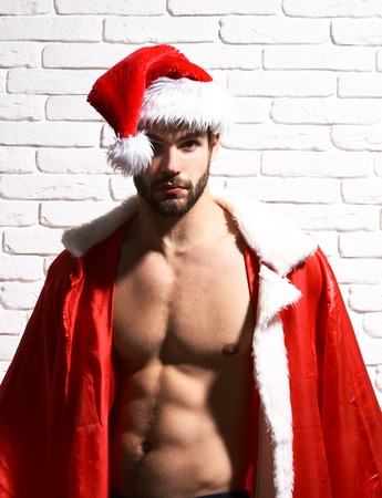 young handsome bearded sexy christmas man with stylish beard in red santa claus hat and coat with muscular bare torso on white brick wall background Stock Photo