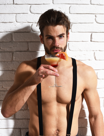 suspender: young handsome bearded sexy macho man with stylish beard shows six packs and abs on muscle torso on athletic body in pants with suspenders holding glass of alcoholic cocktail on brick wall background