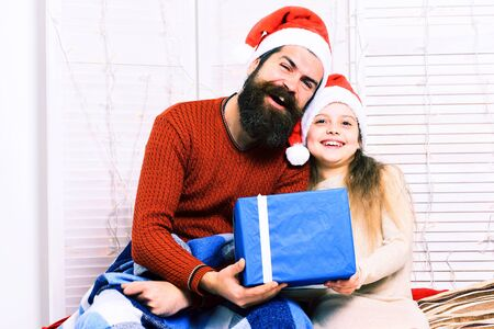 handsome bearded man with long beard in christmas red hat with blue checkered plaid holding big present and cute blonde offended girl in beige dress with crossed hands on white studio background