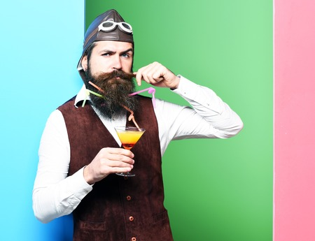 handsome bearded pilot or aviator man with long beard and mustache on serious face holding glass of alcoholic beverage in vintage suede leather waistcoat with hat and glasses on studio background Stock Photo