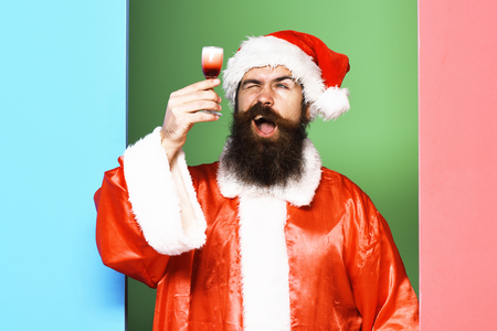 handsome bearded santa claus man with long beard on funny face holding glass of alcoholic shot in red christmas or xmas coat and new year hat on colorful studio background