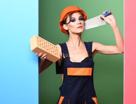 pretty cute sexy builder girl or brunette woman with fashion makeup on serious face in orange uniform hard hat or helmet holding brick and putty knife on colorful studio background