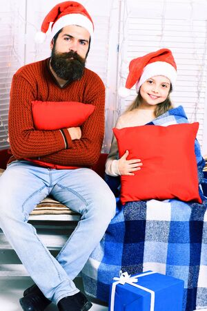 red pillows: handsome bearded man with long beard in christmas hat and cute blonde smiling girl with blue checkered plaid holding red pillows on white studio background