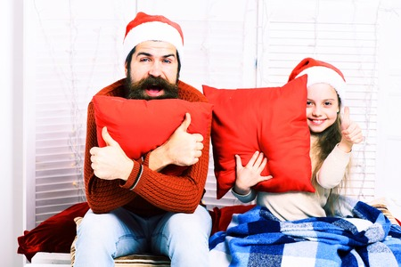 red pillows: handsome bearded man with long beard in christmas hat and cute blonde smiling girl with blue checkered plaid hugs red pillows on white studio background