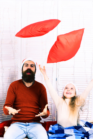 handsome bearded man with long beard in christmas hat and cute blonde smiling girl with blue checkered plaid throw up red pillows on white studio background