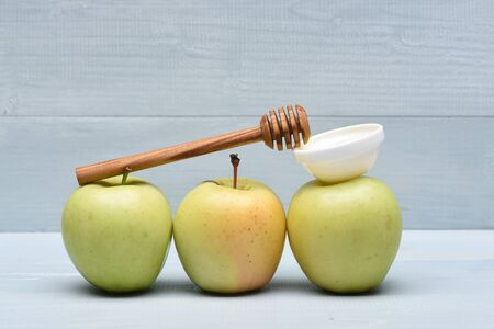 them: Green fresh apples with honey and stick on them on blue vintage wooden background