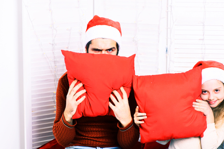 red pillows: handsome bearded man with long beard in christmas hat and cute blonde smiling girl with blue checkered plaid hiding behind red pillows on white studio background