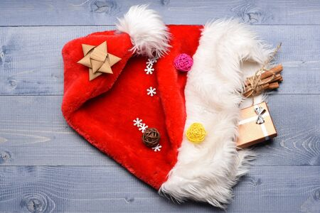 Colorful Christmas or New Year decoration include gift with silver bow, Santa Claus red hat, brown bow, colorful clews, cinnamon with string and snowflakes on blue vintage wooden background Stock Photo
