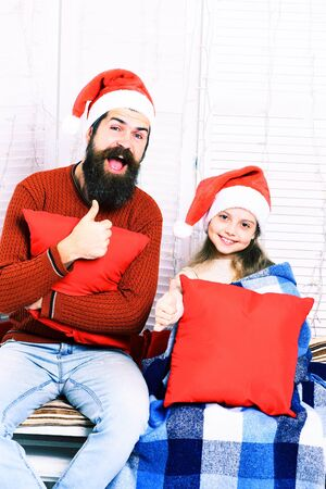 red pillows: handsome bearded funny man with long beard in christmas hat and cute blonde smiling girl with blue checkered plaid holding red pillows on white studio background