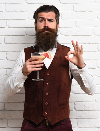 white beard: handsome bearded man with long beard and mustache has stylish hair on serious face holding glass of alcoholic beverage in vintage suede leather waistcoat on white brick wall studio background