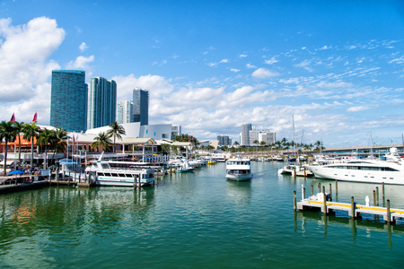 blue vessels: Miami, USA - February 29, 2016: city harbor or port with high buildings and piers with ships marine vessels on sea water surface or moorage on sunny day on blue sky